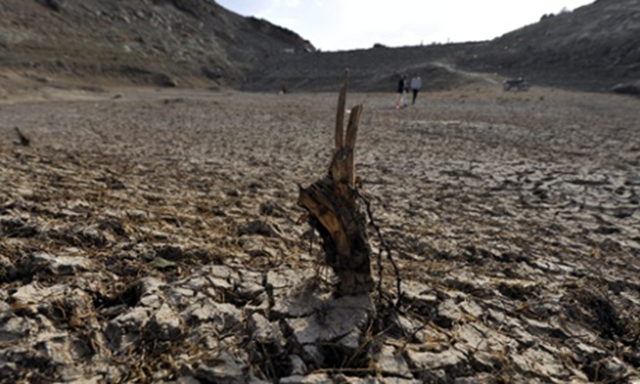 Yemenis walk through a drought-affected dam on the outskirts of Sana'a, Yemen. Sana a city is running out of water and many relief agencies feel that it could become the first capital city in the world to run out of a viable water supply. Photo: Yahya Arhab / EPA