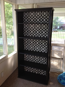 An IKEA Billy Bookcase painted black with a black and white patterned backing