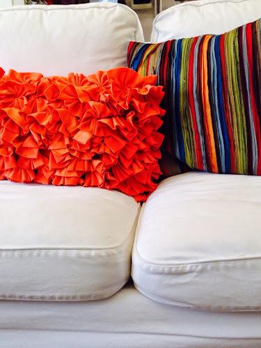Bright bold family room, white sofa bright colored pillows, orange fluffy pillow