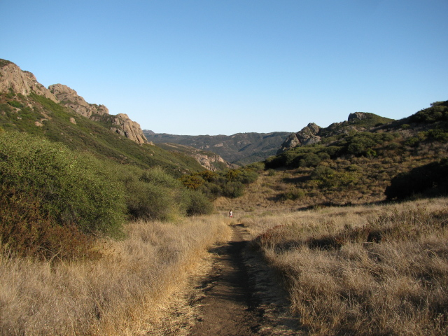 rolling hills with rocky tops at the edges of a grass field with the trail running down it