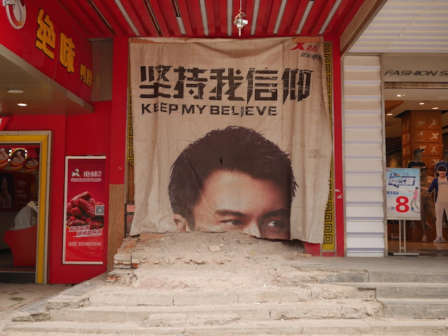"part of large advertisement for Xtep with the message ""KEEP MY BELIEVE"" covering a space apparently under construction"