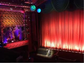 Kinosal med et rødt teppe hengende foran lærettet. Langs veggen er flere stabler med bøker som vi også så i filmen. Under taket henger noen planeter.