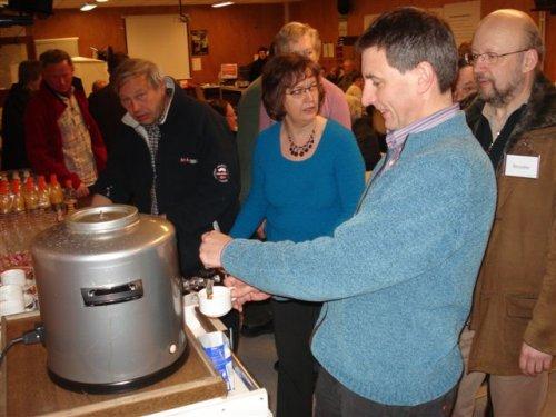 Colruyt ontvangt de bezoekers en biedt hen een drankje aan.