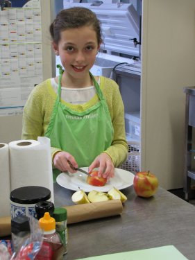 Charlotte snijdt met hoge precisie ultra dunne schijfjes appel.