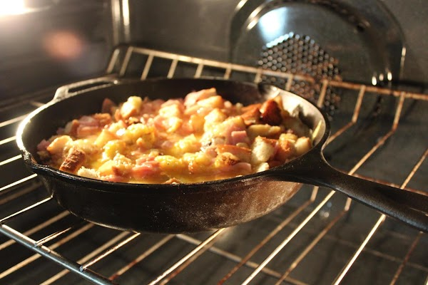 Pour egg mixture over bread and ham in skillet.  Remove skillet from stove...