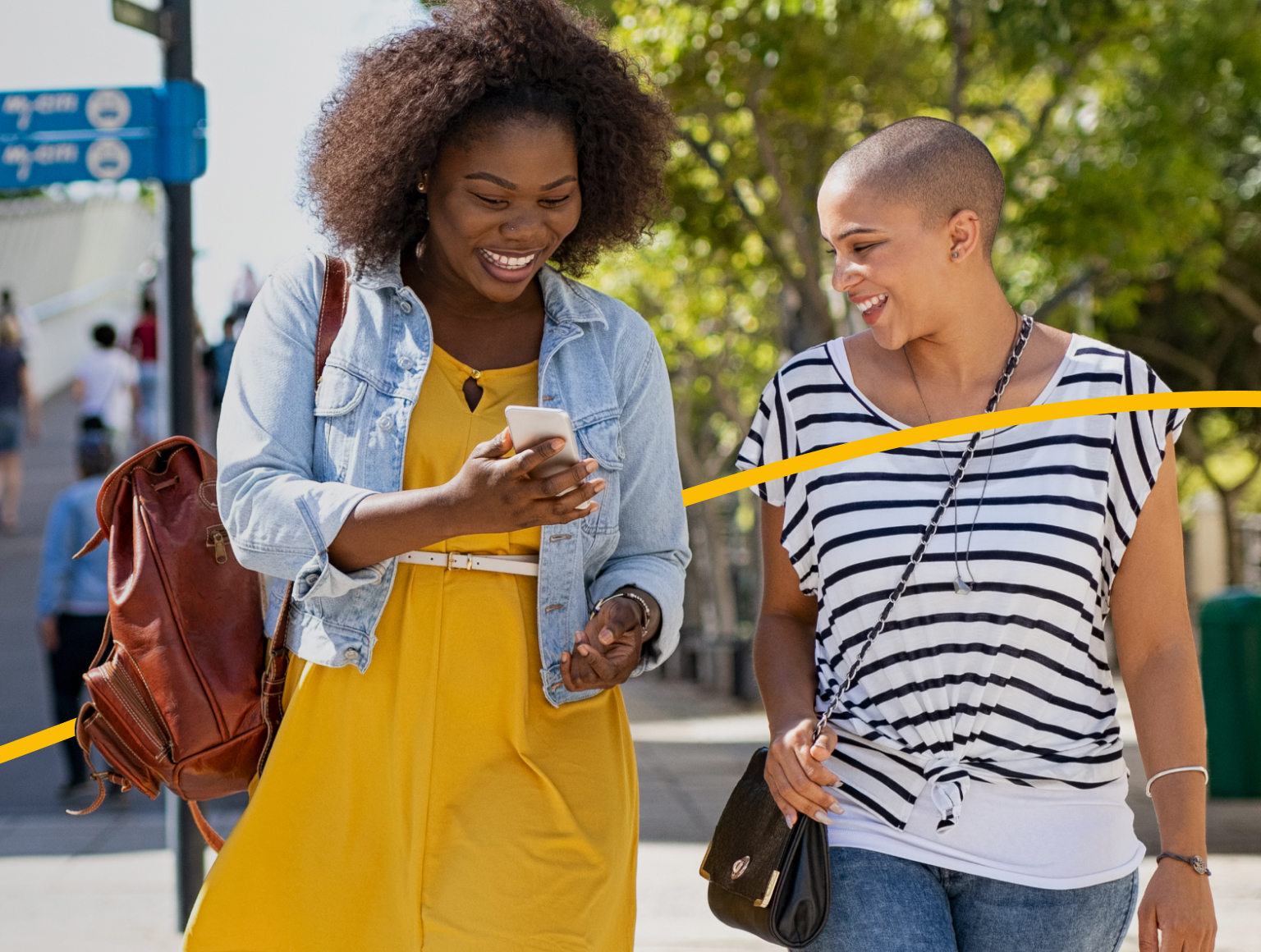 Two women walking in a city looking at a phone