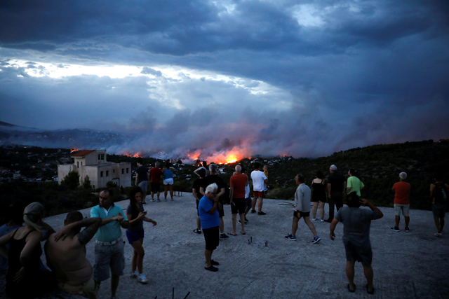 People watch a wildfire raging in Rafina, east of Athens, on 23 July 2018. Photo: Alkis Konstantinidis / Reuters