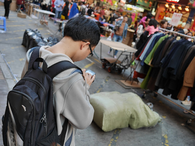 young man checking his mobile phone at Sai Yeung Choi Street South