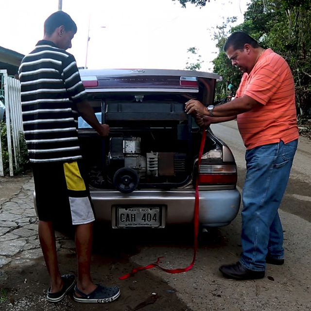 Maria Ortiz Viruet's son, Jesús, works on a gas-powered generator, the only electricity supply for his home in Puerto Rico. Nearly every day, the generator needs some kind of fix. When it breaks down, out come the candles and flashlights. Photo: The Washington Post