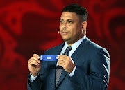 Draw assistant Ronaldo holds up the name Brazil during the South American Zone draw at the Preliminary Draw of the 2018 FIFA World Cup in Russia at The Konstantin Palace on July 25, 2015 in Saint Petersburg, Russia.
