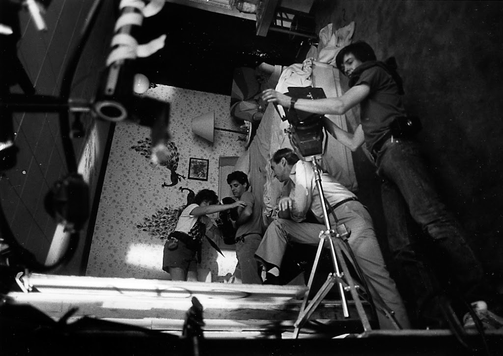 In center Director of Photography Jacques Haitkin and Assistant Camera Anne Coffey prep a shot in the revolving room while Wes Craven looks on.