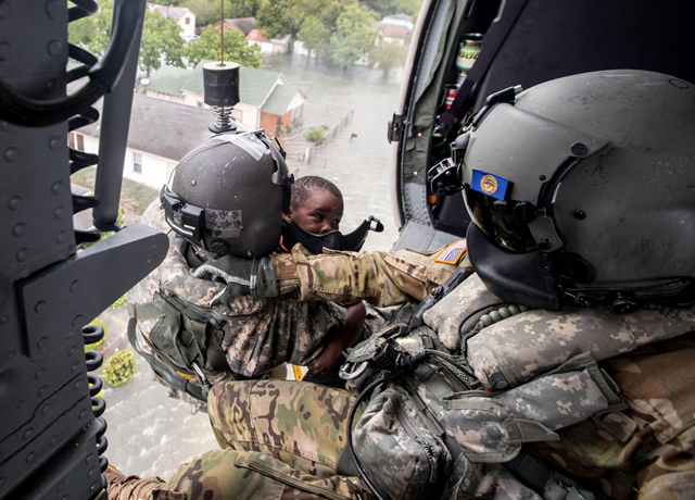 Staff Sgt. Lawrence Lind, left, hoists a child into a Black Hawk helicopter while Sgt. Ray Smith helps the boy who was rescued from Hurricane Harvey floodwaters in Port Arthur, Texas. Photo: Chris Machian / Omaha World-Herald