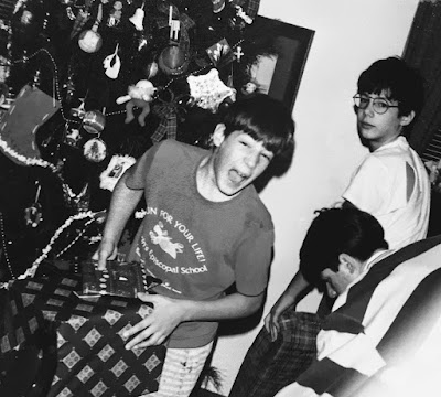 A scanned family photograph of three Roselli brothers opening their gifts one Christmas morning (ca. 1995)