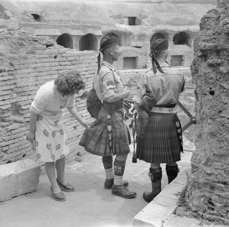 An Italian woman inspects the kilts of Pipe Major William MacConnachie and Pipe Major William Boyd in the Colosseum of Rome, 6 June 1944.