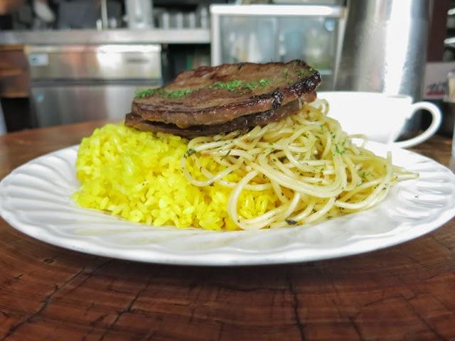 横から見たてんこ盛りの牛肉の薄切りステーキ
