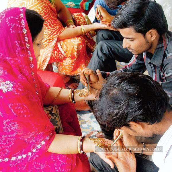 Women getting mehendi done the evening before Teej, in Jaipur.