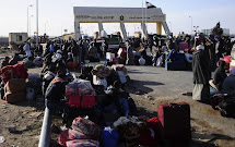 Egyptians wait with their belongings after crossing through the Salum border from Libya into Egypt February 22, 2011. Egypt's new military rulers reinforced their border with Libya on Tuesday and opened the frontier round-the-clock to thousands fleeing th