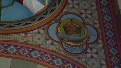 """Na figura: Um peixe sobre as águas, símbolo do Batismo, de que nos fala S. Paulo na epístola do dia, e sobre ele uma cesta transbordante de pães (recolham sete, depois de terem comido), e o monograma de Cristo, que operara o milagre. Na Legenda: """"Et manducaverumt, et saturati sunt"""" (E comeram e ficaram fartos). (Mc. 8, 8)."""