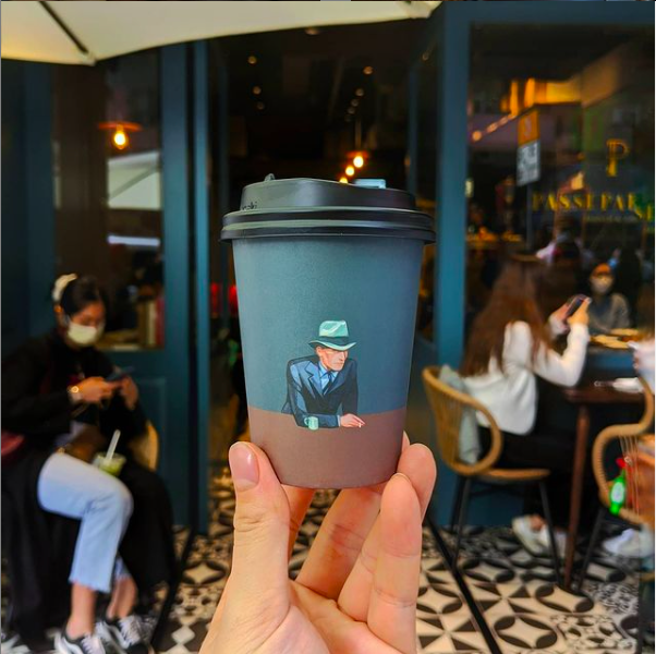 takeaway coffee cup with illustrated design at Passepartout Brunch and Coffee