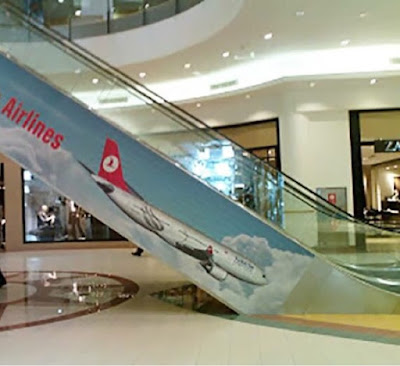 iklan pesawat seolah-olah sedang jatuh ke lantai di sisi tangga berjalan