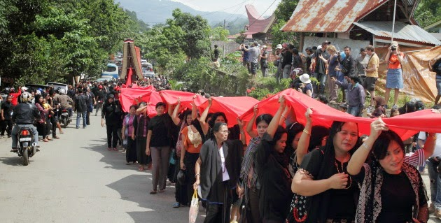 A Torajan funeral ceremony brings traffic to a standstill in Tana Toraja