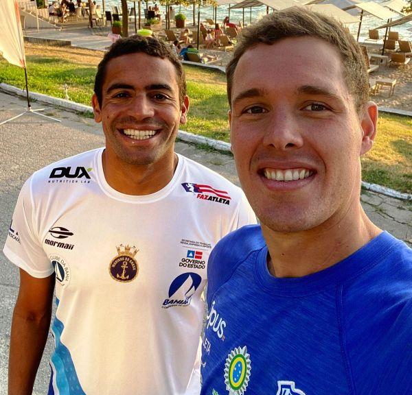 Alan do Carmo, de camiseta branca, e Diogo Villarinho de camisa azul, posam e sorriem para uma selfie
