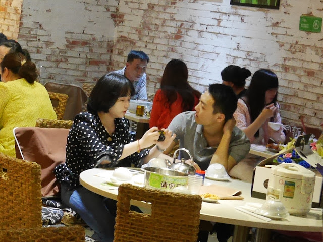 couple sitting at a restaurant table with a rice cooker