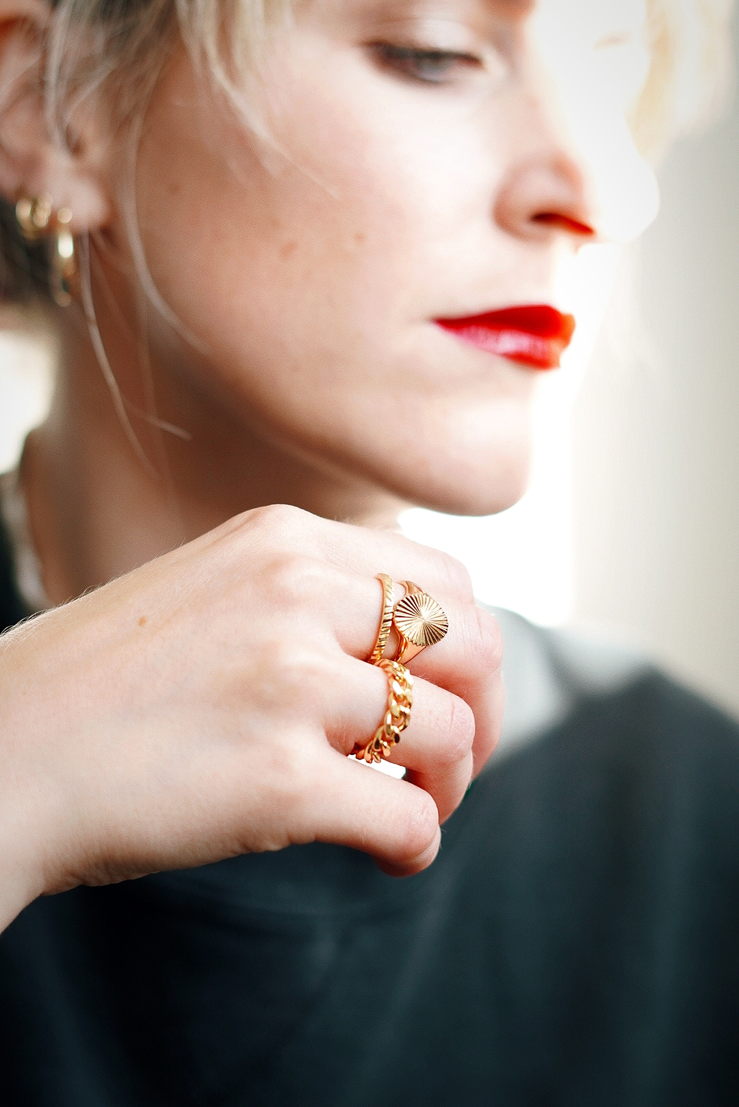 Amy's hand is in focus in front of her face which is not, on her hand are three gold rings; one chain linked, one plain band and one signet ring