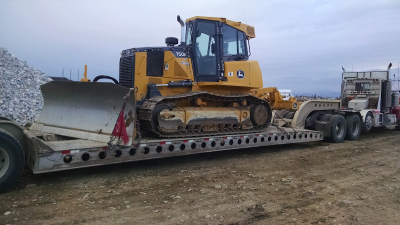 small cat excavator loaded on flatbed trailer