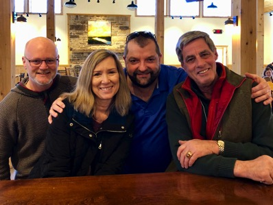 Four friends gathered at a bar for cider sampling