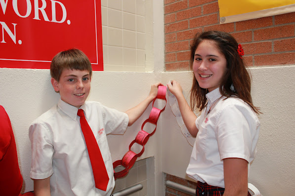 Eighth grader Nicholas Lee and sixth grader Katelyn Ashley help other students hang a prayer chain in the front entryway of the middle school on Monday, January 28, 2013.
