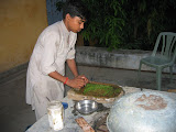One of the kitchen staff prepares fresh green chutney for dinner
