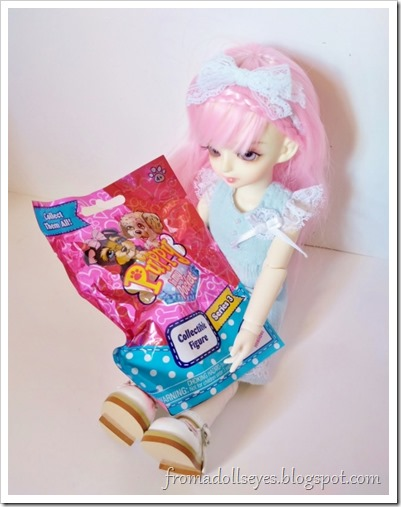 The pink haired doll (Yuna) holding a Puppy in My Pocket blind bag, ready to open it!