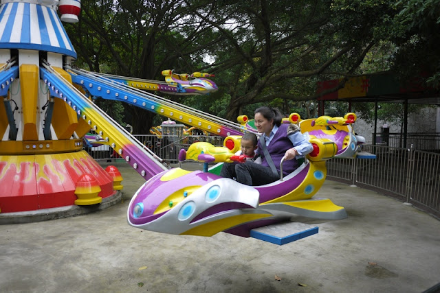 Woman and child on jet amusement park ride in Zhuhai, China