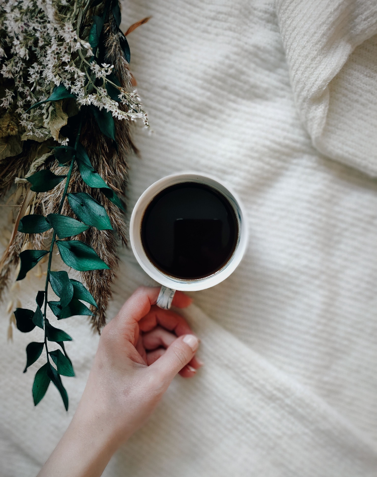 cup of black coffee next to a bouquet of dried flowers