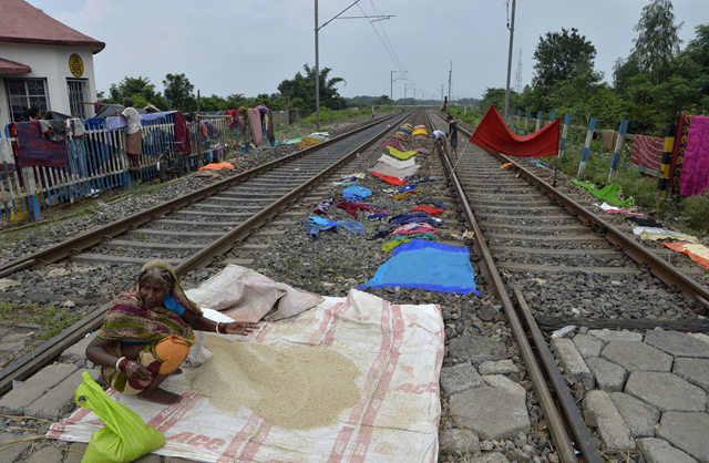 An evacuated woman dried grain on railway tracks in Bihar after being forced from her home by flood waters in August 2017. Photo: Diptendu Dutta / Agence France-Presse / Getty Images