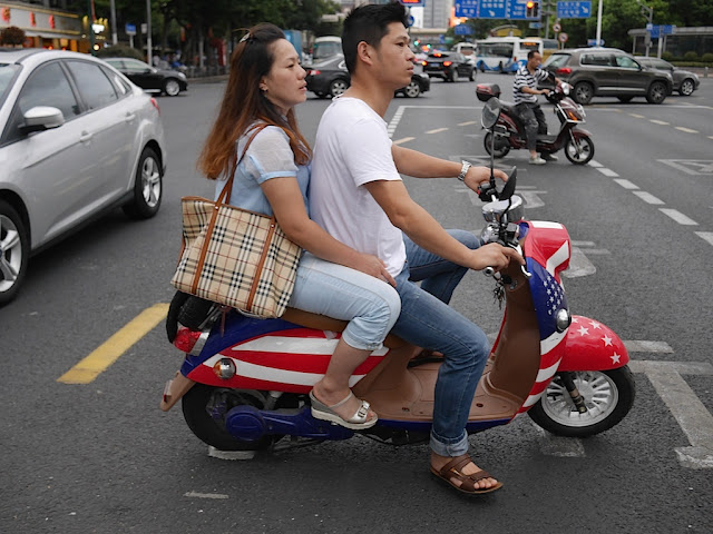 young man and woman riding a motorbike with a U.S. flag design in Shanghai