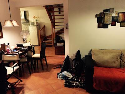 En stue med en trapp og et kjøkken i bakgrunnen.