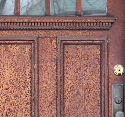 closeup of an antique front door with an interesting nubbly texture to its varnish