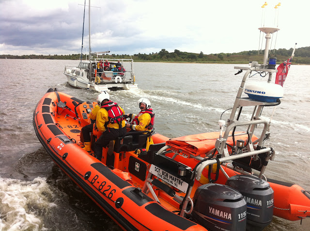 19 July 2012 - Poole inshore lifeboat escorts the catamaran that had gone aground at the entrance to the Wareham Channel. A crew member is onboard checking that all is well. Photo: RNLI/Poole Dave Riley