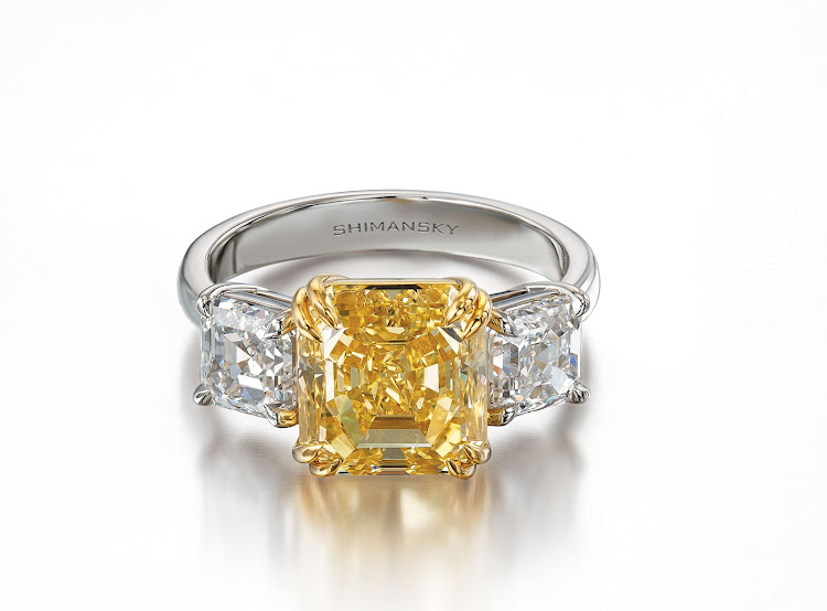 Intense fancy yellow 4.8ct diamond ring in 18k yellow gold, flanked by two 1ct D colour diamonds set in platinum, Shimansky