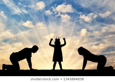 shadow of mum and dad on their knees with child in the middle wearing a crown