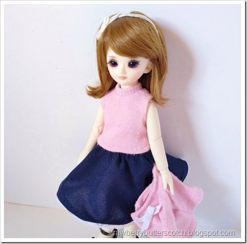 The doll with the sweater removed to show off the sleeveless knit top.