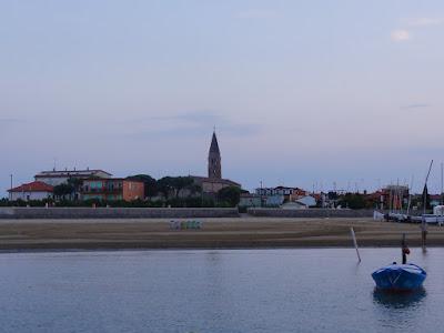 Gammel by med høyt tårn med en strand i forgrunnen.