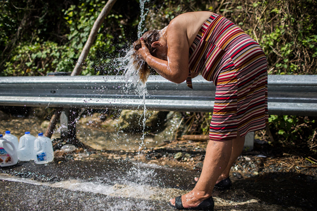 People in Puerto Rico cluster along roadways to bathe and do laundry using water sent down from higher elevations in PVC pipes. Some collect water to take home, for flushing toilets and cleaning. Carmen Rodriguez, 70, bathes using the improvised water system. Photo: Dennis M. Rivera Pichardo / The New York Times