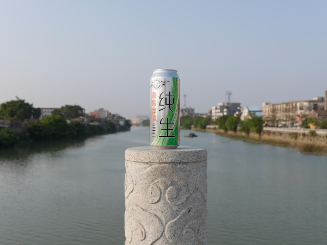 Tall can of Tsingtao Draft beer with the Moyang River in the background