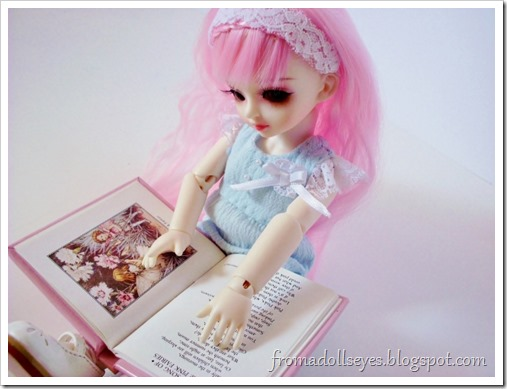A ball jointed doll learning to read.  Reading is for Everyone.
