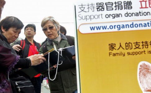 Members of the public sign a donation card during a promotional activity for organ donation. Photo: Felix Wong