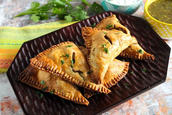 A Platter Of Turkey & Potato Empanadas With Salsa Verde.