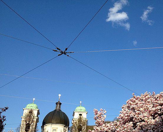 Dreifaltigkeitskirche, Wolken, Magnolien mit Straßenbahn-Oberleitung, Salzburg